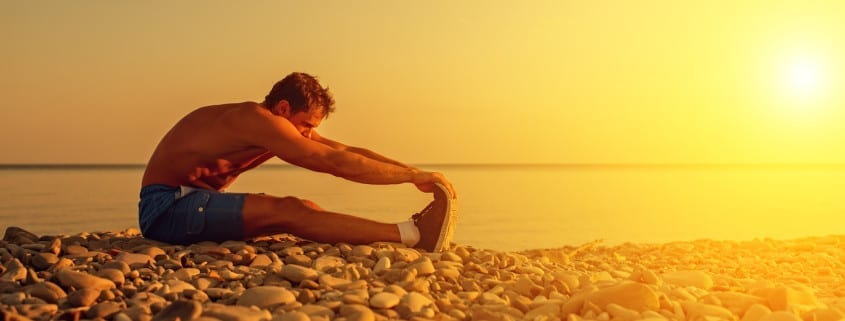 Man stretching on a beach after Male Breast Reduction