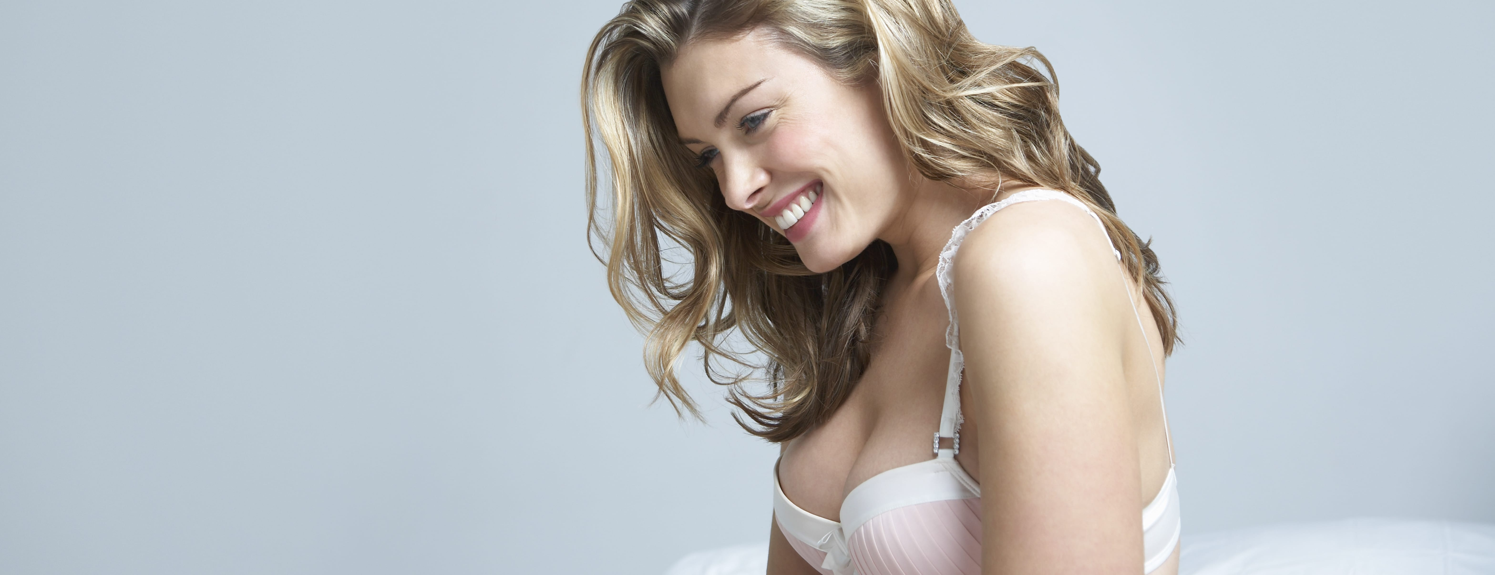 Happy thoughtful woman in bra sitting on bed after Breast Augmentation in Winnipeg, MB