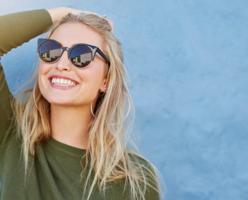 Blonde woman smiling wearing sunglasses looking up