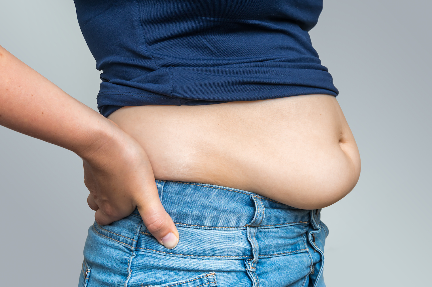 Overweight woman in jeans and fat on hips and belly