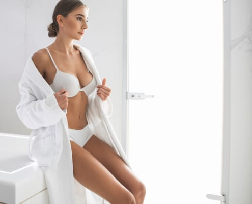 Charming girl in white lingerie and soft bathrobe at plastic surgery clinic looking at size of her breasts