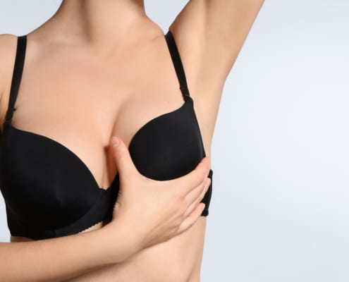 Young woman checking her breast black bra, after breast implants