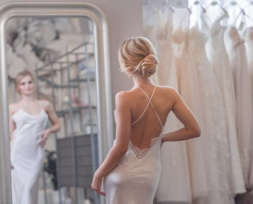 Beautiful bride at the mirror thinking about breast lift surgery
