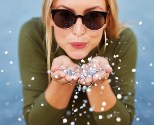 Close up portrait of attractive young woman blowing glitters excited about rewards program. Caucasian Female model having fun over blue background.