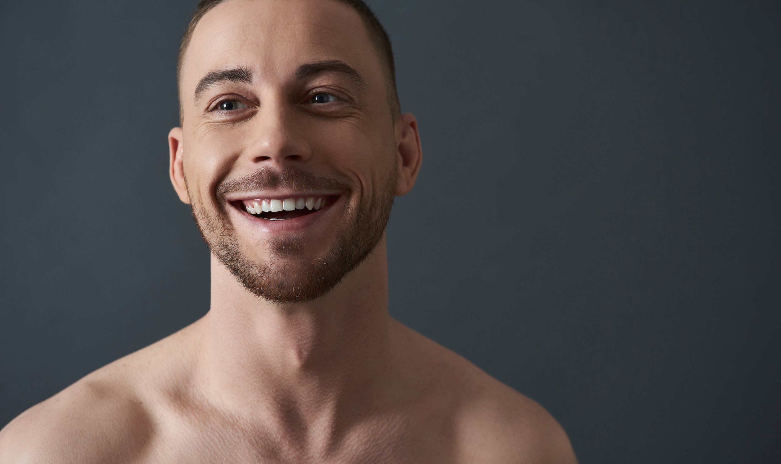 Close up of naked attractive Caucasian guy posing for camera. He is looking away and smiling in studio against gray background. Body care concept