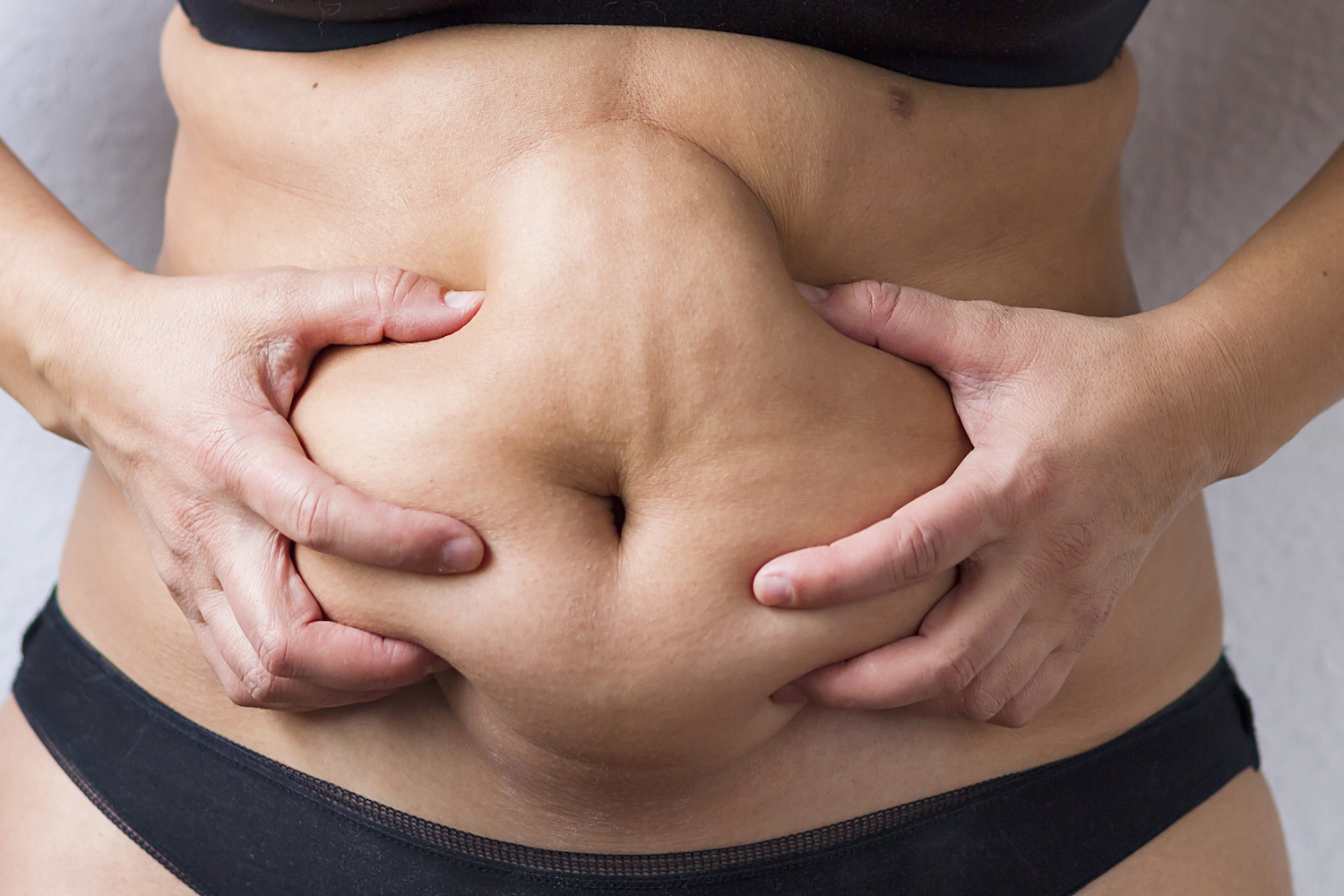 woman squishing loose belly skin