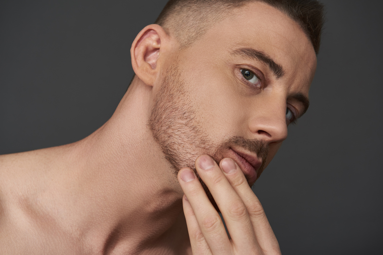 Close up of naked attractive Caucasian guy looking at his jawline in the mirror. He is touching his stubble