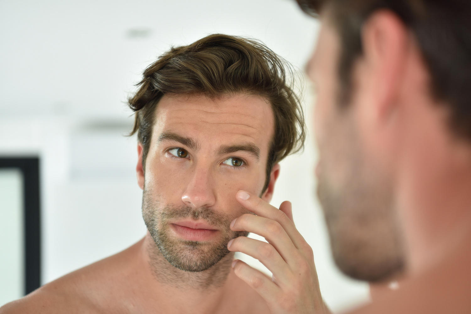 Handsome man looking at cheekbones in front of mirror