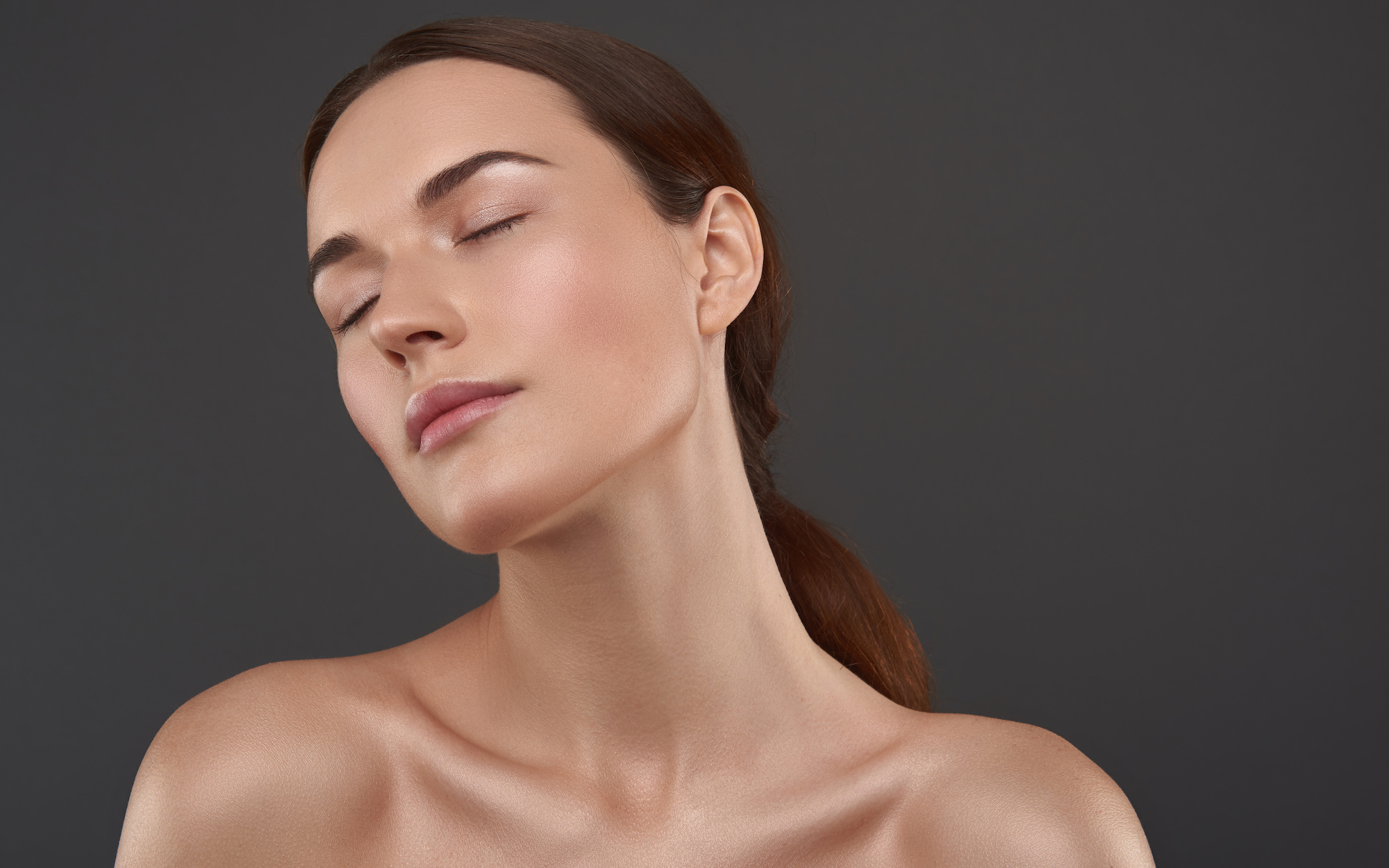 Close up portrait of attractive lady with jawline facing camera, naked shoulders, eyes closed feeling calm and peaceful
